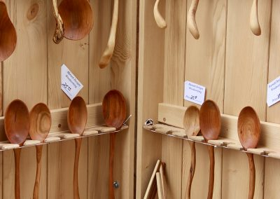 A wooden shelf displaying carved wooden spoons at the Colorscape Chenango Arts Festival