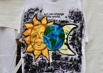 """A painted t-shirt that says """"Art can change the world"""" and showing a sun, Earth, and moon"""