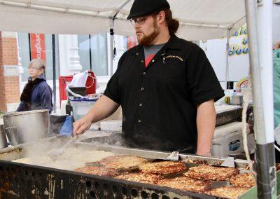 A man cooks food on a large griddle under a tent at the Colorscape Chenango Arts Festival