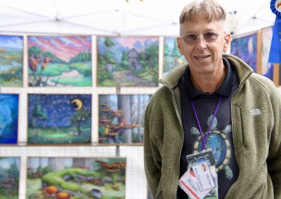 A man smiles in his artist booth next to a blue ribbon, with detailed and colorful paintings in the background