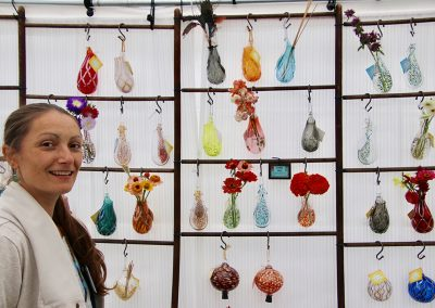 A woman smiles next to colorful glass hanging vases filled with flowers at the Colorscape Chenango Arts Festival