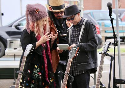 Three musicians look at a piece of paper while standing behind three guitars at the Colorscape Chenango Arts Festival