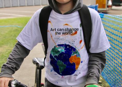 A young man walking his bicycle wears a painted t-shirt at the Colorscape Chenango Arts Festival