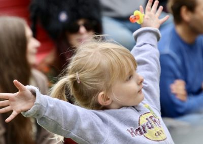 A young girl spreads her arms wide as she watches performers at the Colorscape Chenango Arts Festival