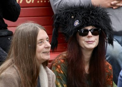 Two women, one wearing a large black fur hat, sit to watch performers at the Colorscape Chenango Arts Festival