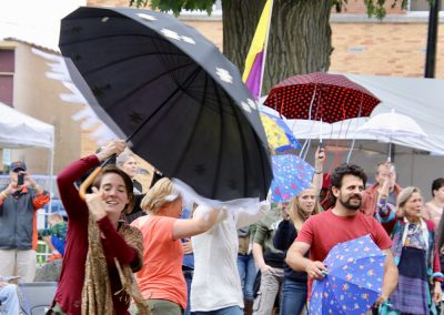 Performers with brightly colored umbrellas move together at the Colorscape Chenango Arts Festival
