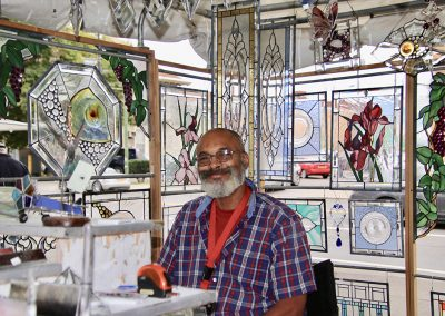 A man smiles in his booth displaying intricate stained glass panels at the Colorscape Chenango Arts Festival