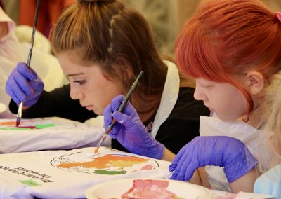 Two young artists paint t-shirts at the Colorscape Chenango Arts Festival Art Zone