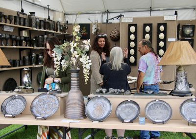 An artist chats with festival attendees in a booth filled with pottery