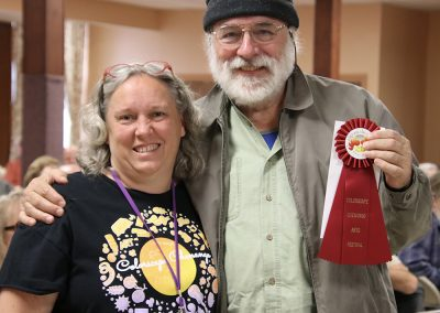 A volunteer and artist smile together with a red ribbon at the Colorscape Chenango Arts Festival artist breakfast