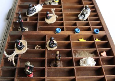 A wooden shelf filled with small trinkets sits on a table at the Colorscape Chenango Arts Festival