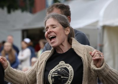 A woman sings and dances wearing a The Trans-Slambovian Bi-Polar Express t-shirt at the Colorscape Chenango Arts Festival
