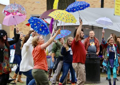 A group of people with brightly colored umbrellas perform together at the Colorscape Chenango Arts Festival