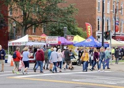 A large crowd crosses the street near food vender booths at the Colorscape Chenango Arts Festival
