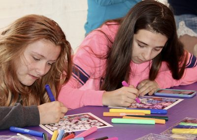 Two young women color in an illustration at the Colorscape Chenango Arts Festival Art Zone