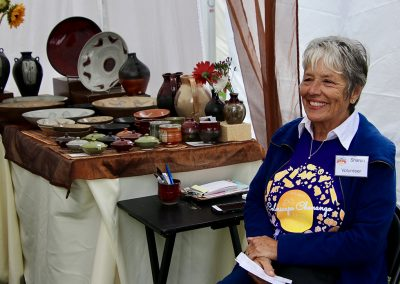 A volunteer sits in an artist booth at the Colorscape Chenango Arts Festival