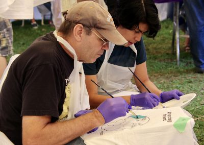 Two attendees paint t-shirts with the Earth on them at the Colorscape Chenango Arts Festival Art Zone