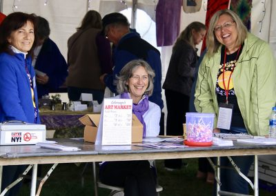 Three volunteers smile at a table at the Colorscape Chenango Arts Festival Art Market