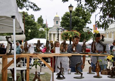Festival attendees admire detailed sculptures and carvings at the Colorscape Chenango Arts Festival