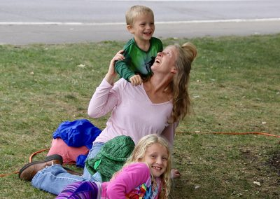 A mother and her two children sit on the lawn laughing at the Colorscape Chenango Arts Festival