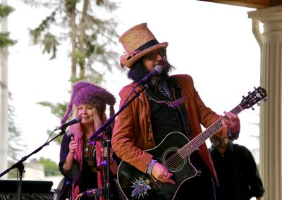 Two musicians wearing fanciful hats perform at the Colorscape Chenango Arts Festival