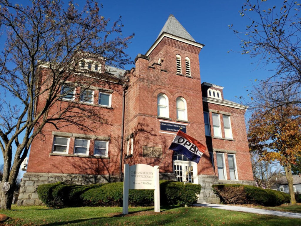"""The Chenango Historical Society, a large brick building with many windows, displays an """"open"""" flag out front on a sunny day"""