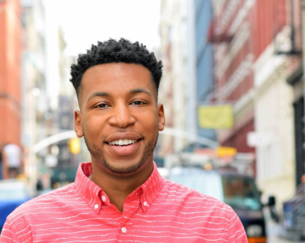 Drew Drake, a young Black actor, poet, and educator, smiles on the street in New York City